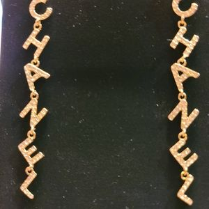 Gold tone long spelled out Chanel earrings